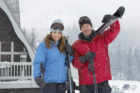 Couple holding skis standing in front of cabin in snow Stock Photo - 8844481
