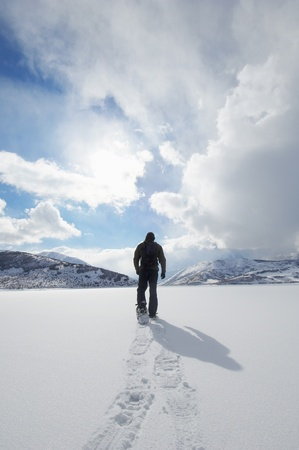 adult footprint: Man walking in snowshoes through snow back view