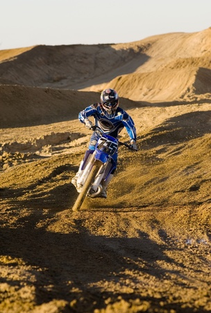 Motocross racer riding on dirt track Stock Photo - 8844502