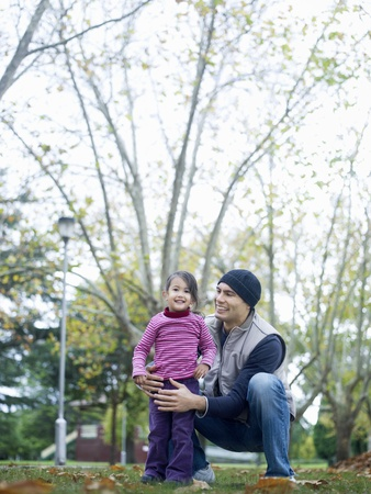 Girl (3-4) standing with father squatting in park Stock Photo - 8822414