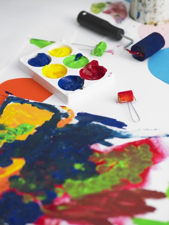 Paints and painting rollers lying next to painting elevated view Stock Photo - 8822417