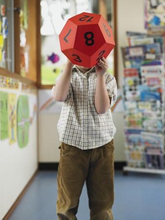 oversize: Boy holding oversize twelve-sided dice in classroom LANG_EVOIMAGES
