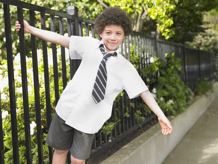 School boy hanging off iron fence Stock Photo - 8844536