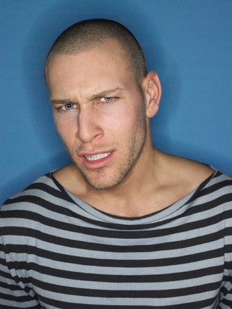 Man in stripy top frowning in studio Stock Photo - 8844575