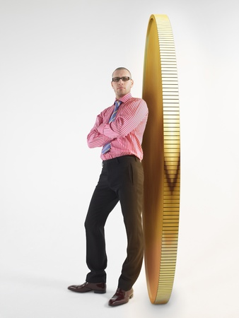 digital composite: Man in glasses leaning against giant coin digital composite