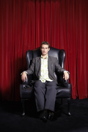 stylishly: Stylishly dressed Man sitting in Wingback Chair in front of curtain