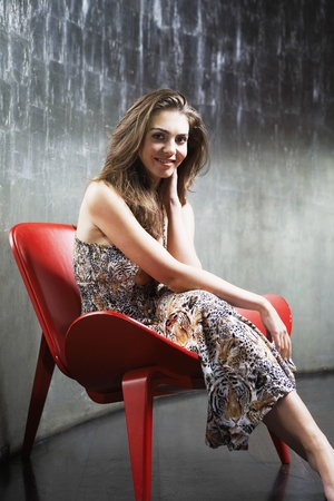 Stylish Young Woman sitting in stylized chair legs crossed hand on neck smiling in metal room portrait Stock Photo - 8844597