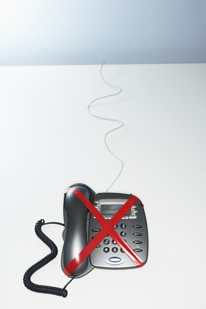 Red tape forming a letter x on telephone elevated view Stock Photo - 8844606
