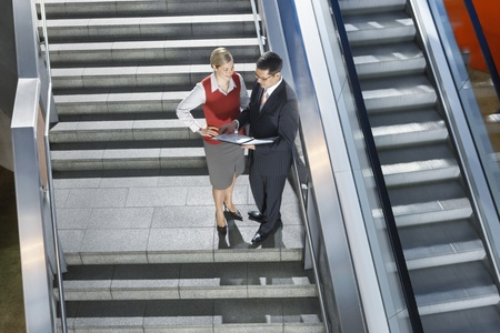 elevated view: Businessman and businesswoman conversing on stairs elevated view