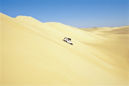 implied: Jeep driving down sand dune