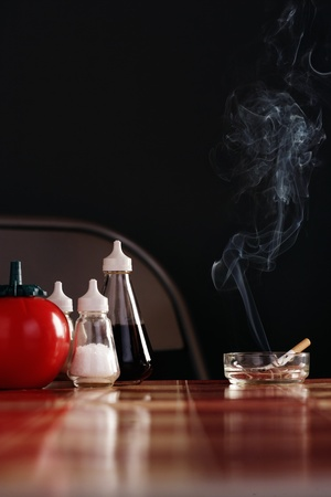 Smoking cigarette in ashtray on table with condiments Stock Photo - 8844735