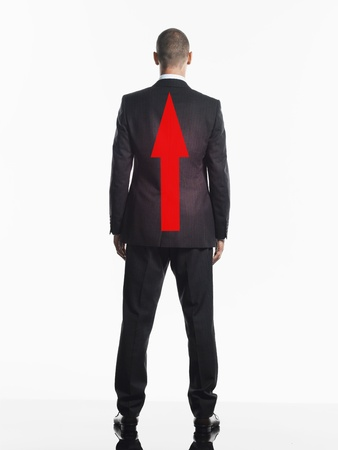 upwardly mobile: Young businessman with red Arrow on Back back view