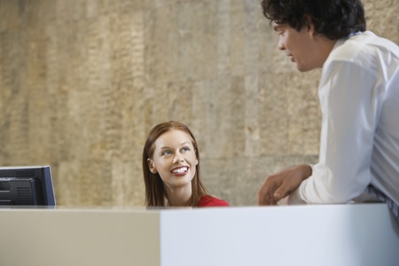 Woman sitting behind desk smiling up at man Stock Photo - 8844795