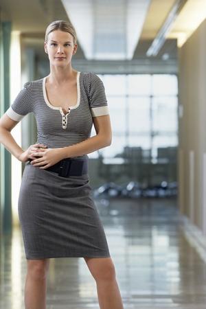 jambes �cart�es: Femme d'affaires debout dans le bureau corridor portrait