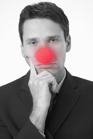 foolishness: Businessman with head in hands wearing Clown Nose portrait