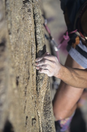 clinging: Rock Climber holding on to cliff close-up