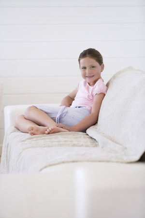 knees bent: Girl sitting on sofa full length eye contact