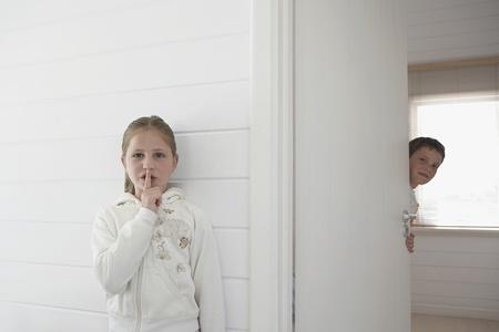 Girl with finger on lips standing by boy peeking round door Stock Photo - 8844839
