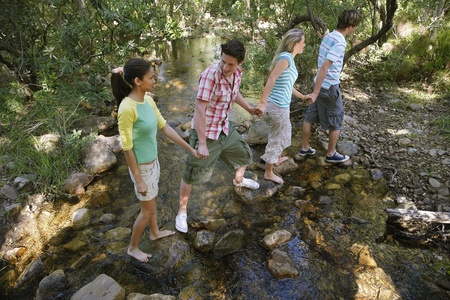 elevated view: Four teenagers (16-17) crossing stream holding hands elevated view