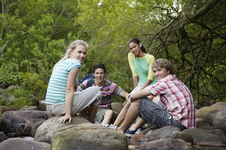 Portrait of four teenagers (16-17 years) sitting on stones by river smiling Stock Photo - 8844865