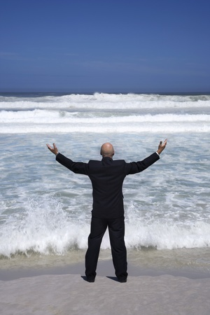 Business man standing on edge of sea arms outstretched back view Stock Photo - 8844884