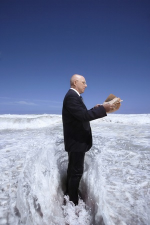 Senior business man reading newspaper standing in ocean wave side view Stock Photo - 8844885