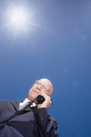 Busieness man using phone standing against sky low angle view Stock Photo - 8844887