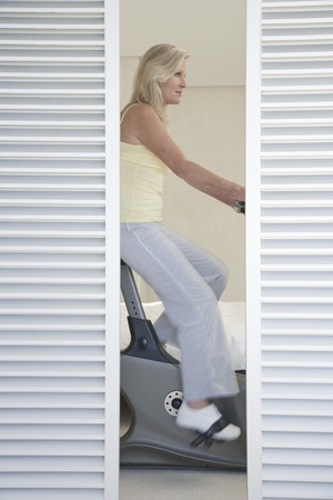 Mature woman on exercise bike behind blinds pedalling side view Stock Photo - 8844892