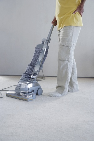 carpet clean: Mature man vacuuming carpet holding lower back in pain low section