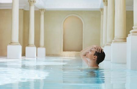 Jonge man met de hand op het hoofd in zwembad zijaanzicht