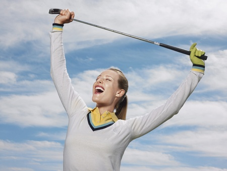 Happy female golfer holding club against sky Stock Photo - 8844900