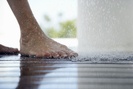 floor standing: Woman standing under outdoor shower close up of feet low section