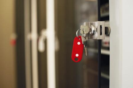 or lock up: Claves con llavero rojo en primer plano de bloqueo.