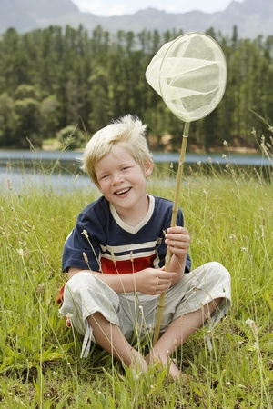 butterfly net: Boy (7-9) sitting in field holding butterfly net front view. LANG_EVOIMAGES