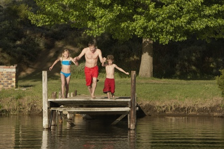 lake front: Two children (7-9) holding hands with father jumping into lake.