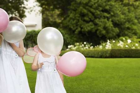 Two young girls in garden wearing white dresses holding balloons Stock Photo - 8844963