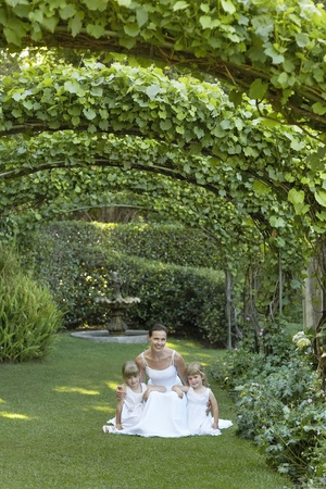 pergola: Two young girls and mid adult bride squatting under ivy arches portrait