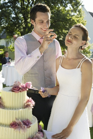Mid adult bride and groom cutting wedding cake groom putting bit of cake on bride's nose Stock Photo - 8844965