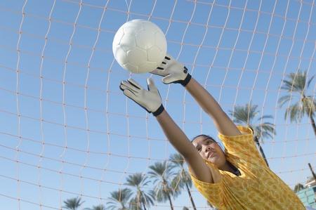 goal keeper: Meisje bereiken voor Soccer Ball
