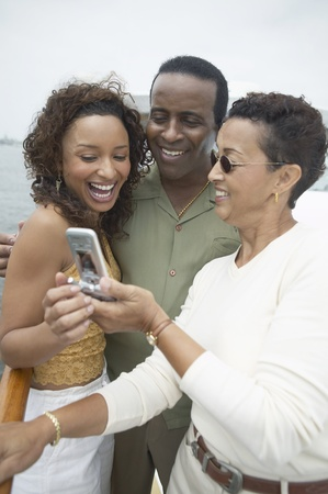 seres vivos: Tres amigos utilizando teléfono celular en yate