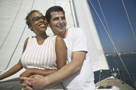 racially diverse: Affectionate Couple Relaxing on Yacht LANG_EVOIMAGES