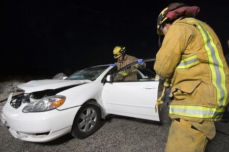 Firefighters examine car after crash Stock Photo - 12513683