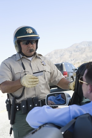 Highway patrol officer examines man's driving license Stock Photo - 12513697