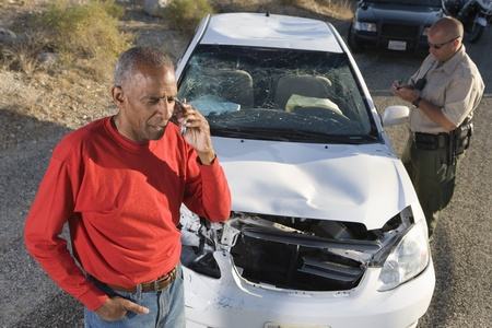 car crime: Man with police officer on mobile phone following car accident