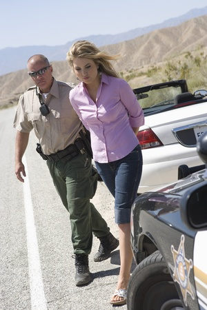 Police officer arresting female driver Stock Photo - 12513744