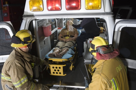 Firefighters looking at victim in ambulance Stock Photo