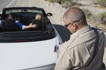 Police officer takes down car details Stock Photo