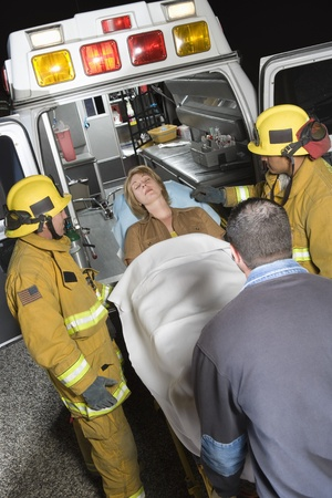 riverside county: Firefighters and paramedic lifting woman into ambulance LANG_EVOIMAGES