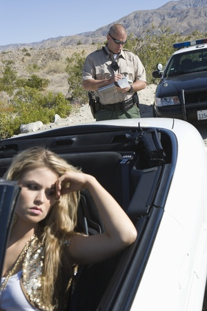 Police officer takes details of vehicle with female driver Stock Photo - 12513775