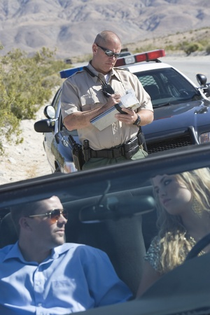 Police officer checks details of vehicle with couple driving Stock Photo - 12513777